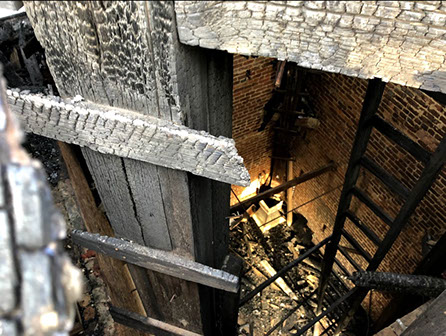 Downward view from scaffold of burnt materials to ground floor level, showing extent of fire damage.