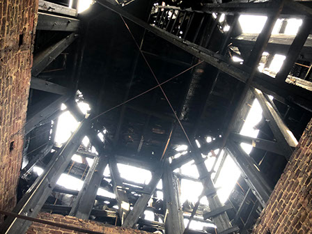 View looking up inside steeple, showing extent of damage by fire.