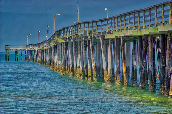 Closeip view of the pier which shows pilings worn and rotted over time from severe weather and harsh salt-sea environment.