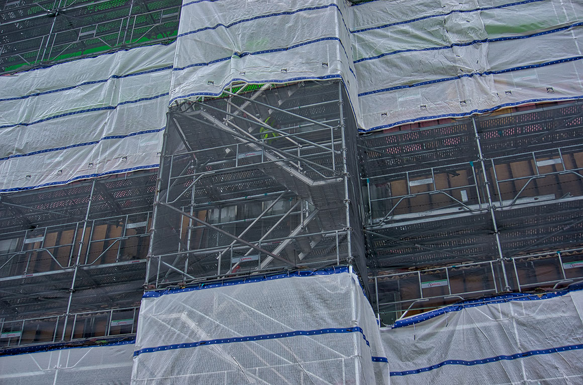 Closeup photo showing scaffolding structure behind safety screen in select demolition of Ivy Tower, Hampton VA
